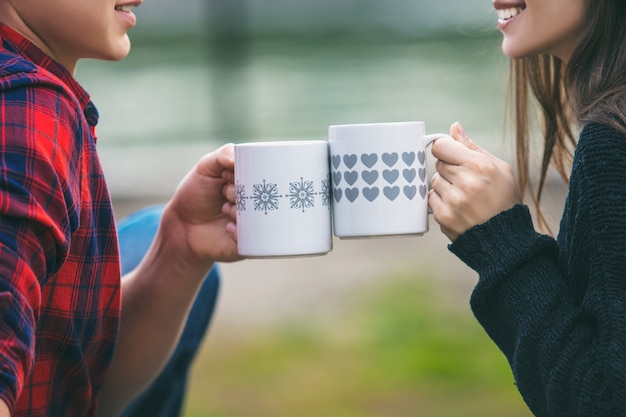 Couple homme et femme jeune beau heureux assis sur une couverture sur l'herbe dans la nature avec des tasses avec des boissons chaudes mains se bouchent