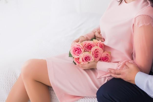 Couple homme et femme, jeunes mariés tenant un bouquet de roses roses.