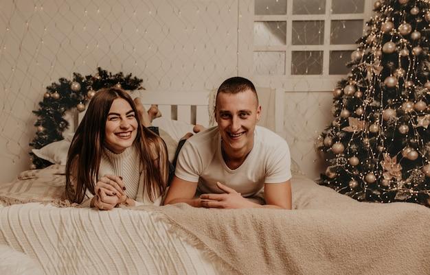 Couple homme et femme se trouvent sur la chambre à coucher près de l'arbre de noël. maison décorée pour le nouvel an