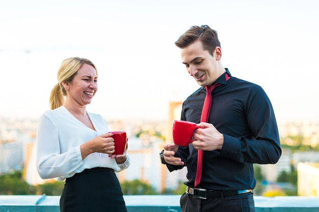 Couple d'hommes d'affaires, bel homme brune et jolie femme blonde se tiennent sur le toit et boivent du café