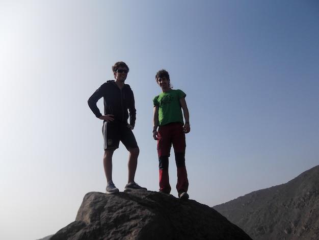 Un couple d'hommes debout sur une colline de pierre