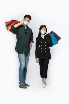 Un couple d'hommes et de femmes portant des masques et transportant beaucoup de sacs en papier pour faire du shopping