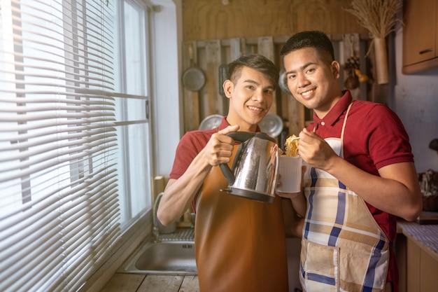 Couple homosexuel masculin cuisinant une tasse de nouilles instantanée