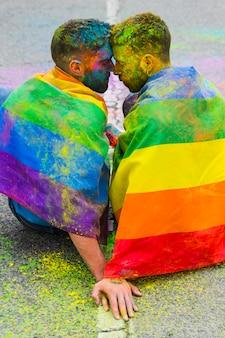 Couple homosexuel reliant les fronts assis sur la route