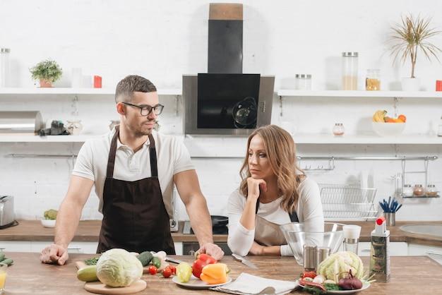 Couple avec des ingrédients dans la cuisine