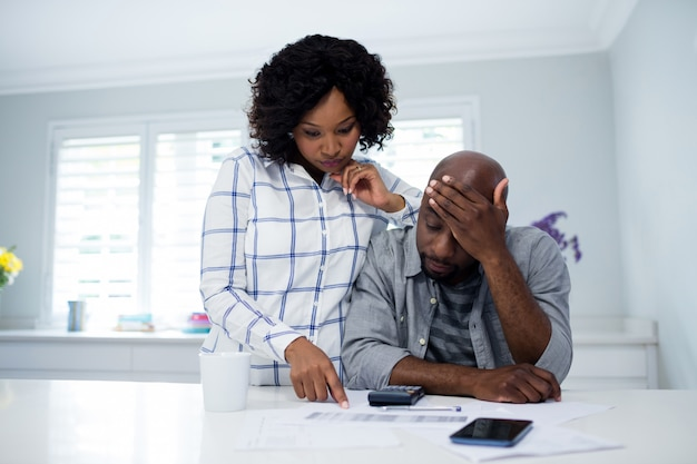 Couple inquiet interagissant tout en vérifiant les factures
