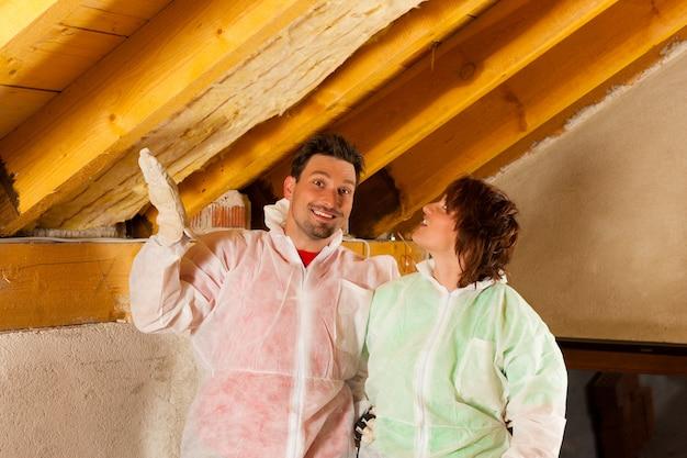 Couple installant une isolation thermique sur le toit