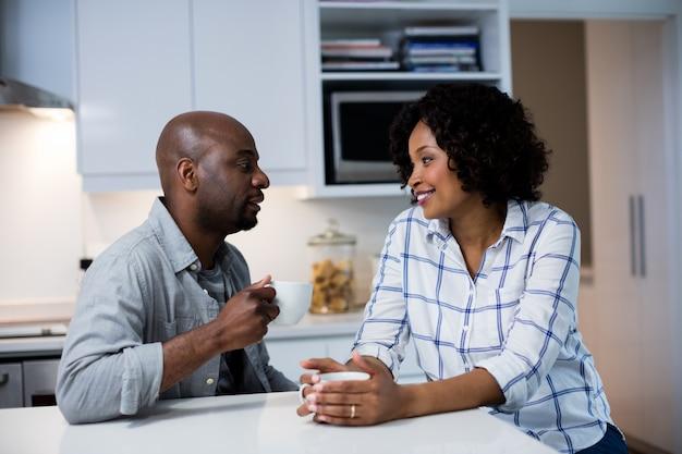 Couple en interaction les uns avec les autres tout en buvant un café dans la cuisine