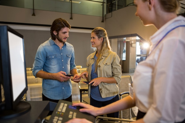 Couple interagissant les uns avec les autres au comptoir d'enregistrement