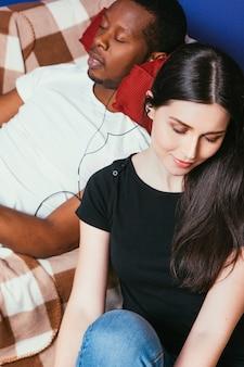 Couple international jeune blanc noir reste musique écouteurs loisirs se détendre convivialité idylle plaisir concept