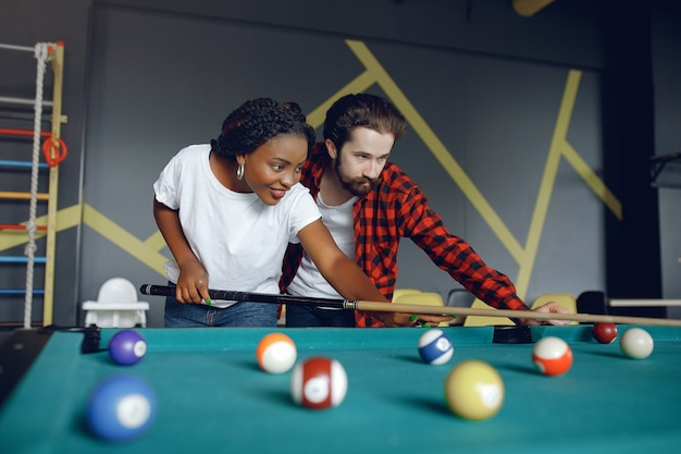 Couple international jouant au billard dans un club