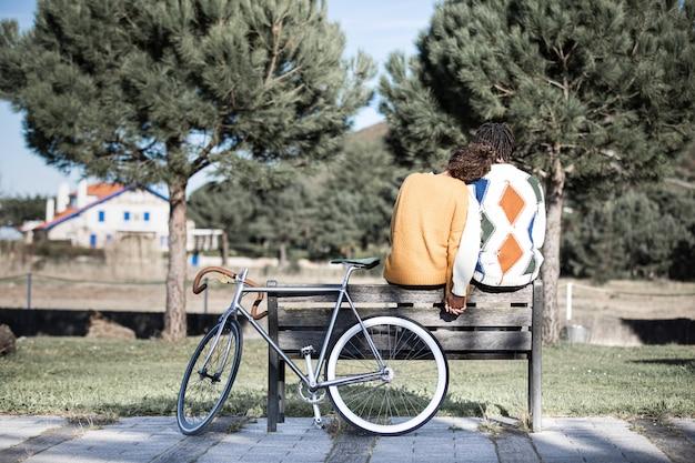 Couple interracial amoureux se tenant la main assis sur un banc dans un parc à côté de leur vélo