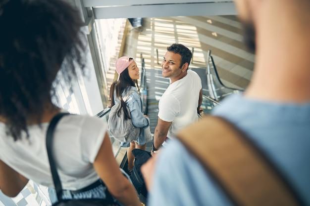 Un couple interracial attrayant et excité sourit alors qu'ils partent en vacances
