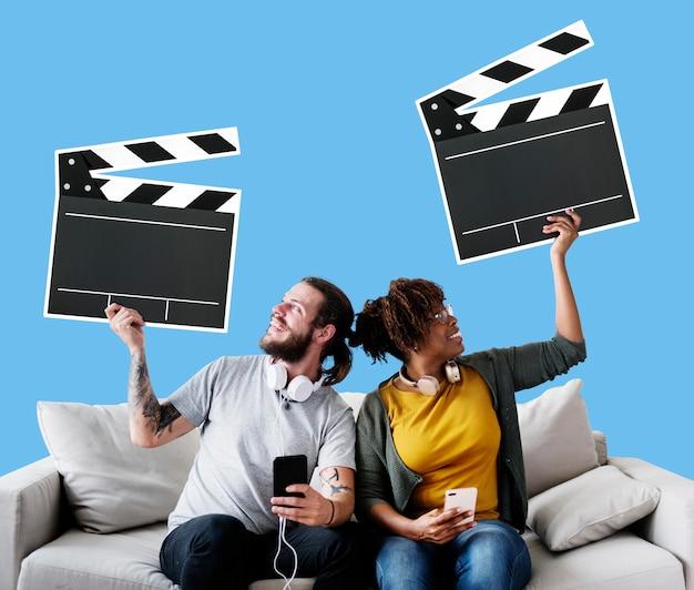 Couple interracial sur un canapé tenant des icônes de clap