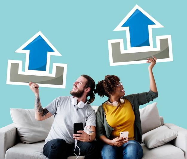 Couple interracial sur un canapé tenant des icônes de téléchargement