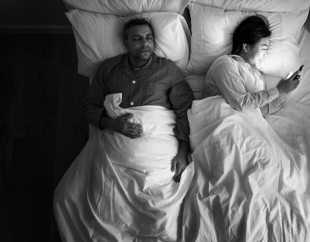 Couple interracial sur la femme du lit en utilisant son téléphone