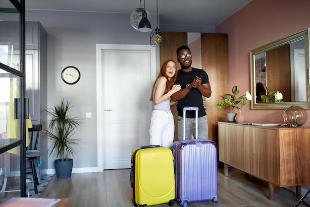 Un couple interracial joyeux entre dans un nouvel appartement