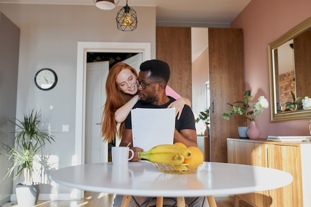 Couple interracial lire le courrier et vérifier la comptabilité dans la cuisine à la maison