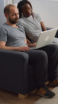 Couple interracial moderne saluant la vidéoconférence