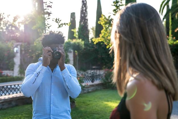 Couple interracial prenant des photos avec un appareil photo vintage. mec noir prenant des photos de fille.