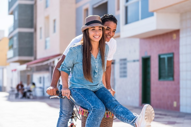 Couple interracial s'amuser ensemble à vélo en plein air dans la ville - bonheur et joie jeunes copain et petite amie interraciaux - deux aiment le mode de vie actif et l'amour ou l'amitié