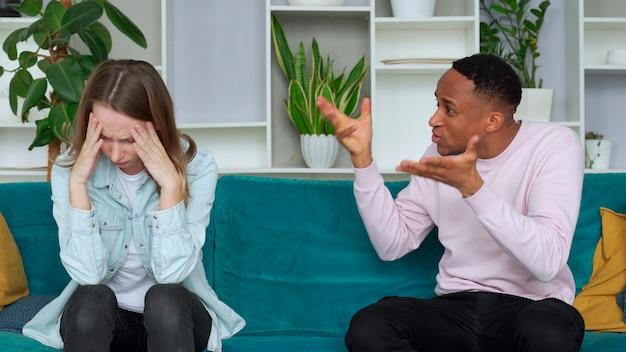 Couple interracial se battre à la maison petit ami criant à petite amie, elle met sa main sur sa tête couple stressé ayant des problèmes concept de divorce