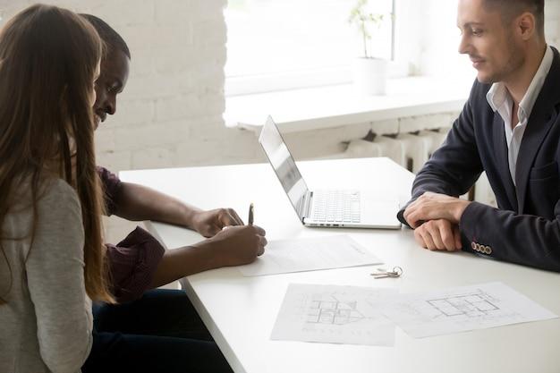 Couple interracial signant un contrat d'investissement hypothécaire lors d'une réunion avec un courtier