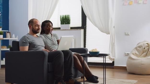 Couple interracial utilisant la communication par appel vidéo à la maison