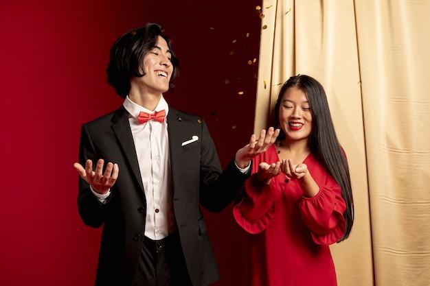 Couple jetant des confettis dorés dans les airs