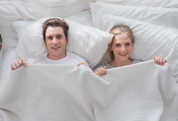Couple jeune amoureux souriant couché sous une couverture blanche au lit