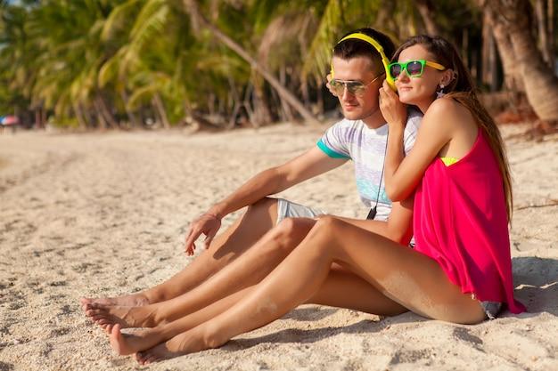 Couple jeune hipster amoureux, plage tropicale, vacances, style branché d'été, lunettes de soleil, écouteurs