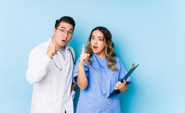 Couple de jeune médecin posant dans un mur bleu isolé ayant une idée, un concept d'inspiration.