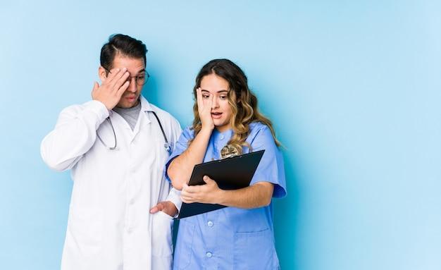 Couple de jeune médecin posant dans un mur bleu isolé cligner des yeux effrayé et nerveux.
