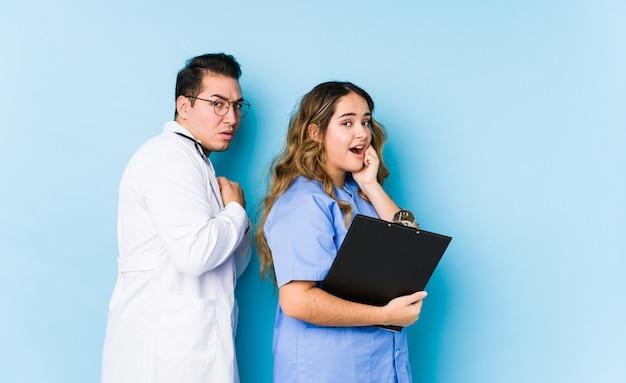 Couple de jeune médecin posant dans un mur bleu isolé effrayé et effrayé.