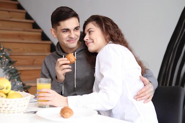 Un couple de jeunes amoureux s'embrassent au petit déjeuner