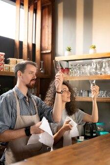 Couple de jeunes entrepreneurs entreprenants assis au comptoir dans un café moderne et utilisant un ordinateur portable tout en discutant du projet