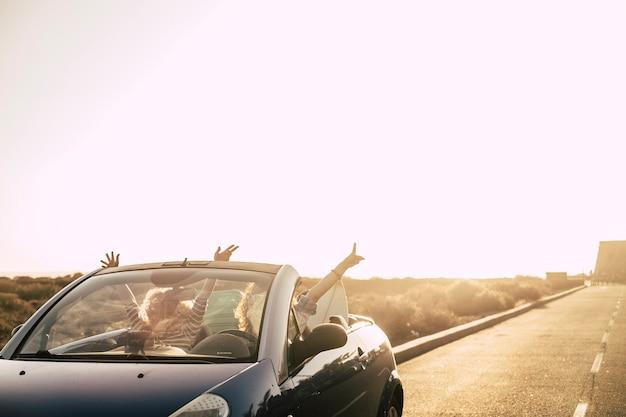 Couple de jeunes femmes adultes sur une voiture décapotable conduisant une longue route avec désert