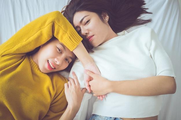 Couple de jeunes femmes allongé sur le lit avec un moment de bonheur.