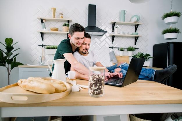 Couple de jeunes gays utilisant un ordinateur portable ensemble à la cuisine. heureux ensemble, concept gay