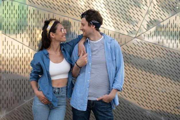Un couple de jeunes hipsters porte des vêtements à la mode et un bandana se regarde heureux souriant à l'extérieur