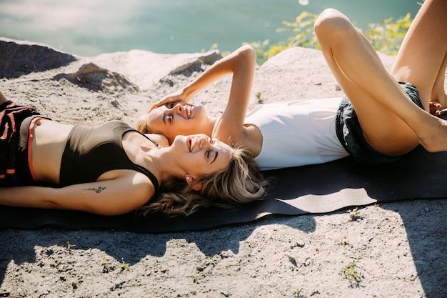 Couple de jeunes lesbiennes s'amusant au bord de la rivière en journée ensoleillée