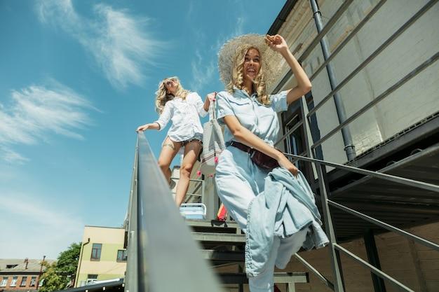 Couple de jeunes lesbiennes se préparant pour un voyage de vacances sur la voiture en journée ensoleillée