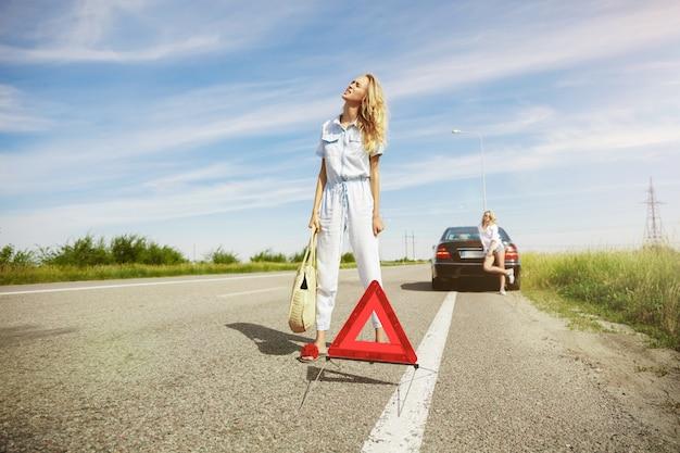 Couple de jeunes lesbiennes en voyage de vacances sur la voiture en journée ensoleillée