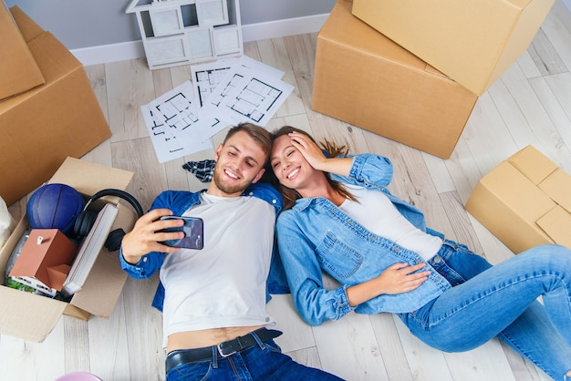 Couple de jeunes mariés allongé sur le plancher en bois de leur nouvel appartement et faisant selfie par téléphone intelligent. vue de dessus.