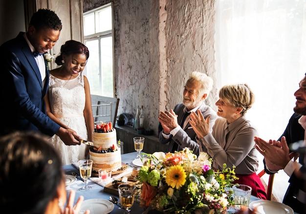 Couple de jeunes mariés coupant le gâteau ensemble