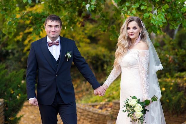 Couple de jeunes mariés dans le jardin lors d'une promenade de mariage