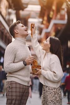 Couple de jeunes mariés manger des nouilles avec des baguettes à shanghai à l'extérieur d'un marché alimentaire