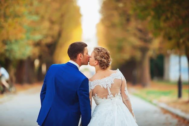 Couple de jeunes mariés marchant dans le parc
