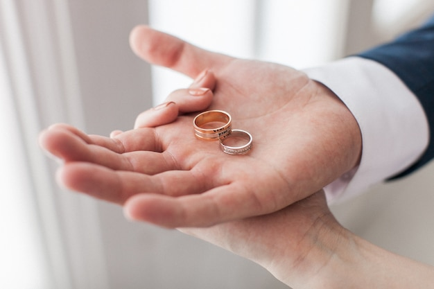 Couple de jeunes mariés montrant dans leurs mains deux anneaux de mariage. groom holding on the palm paire d'anneaux de mariée avec une inscription en latin:
