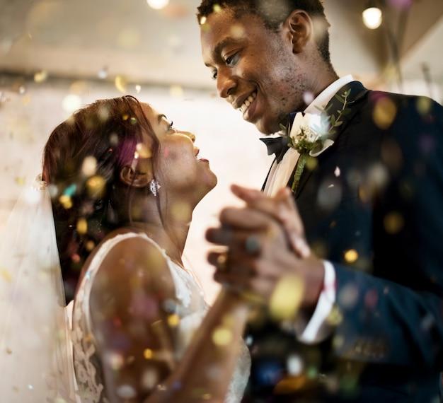 Couple de jeunes mariés d'origine africaine dansant célébration de mariage